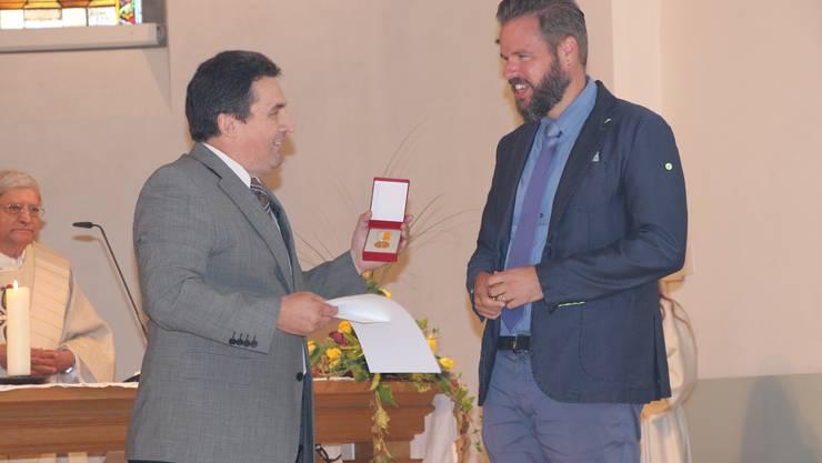 Kirchgemeindepräsident Daniel Meister übergibt Simon Haefely die Ehrenmedaille