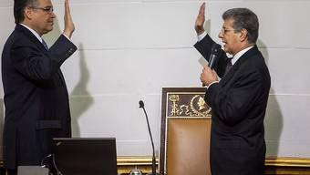 Der neue Parlamentspräsident Venezuelas, Henry Ramos, bei der Vereidigung der Parlamentsabgeordneten.(Archiv) Mit der umstrittenen Vereidigung dreier Parlamentarier, deren Wahl vom Obersten Gericht zuvor suspendiert worden war, errang die konservative Opposition eine Zweidrittel-Mehrheit.