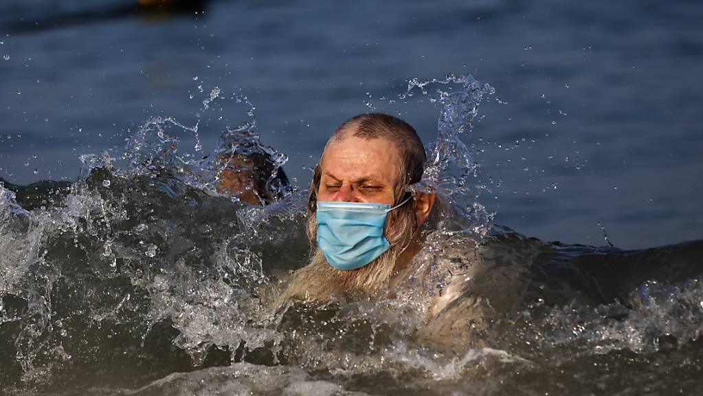 Ein Mann schwimmt mit Mundschutz an einem Strand in Tel Aviv. Foto: Oded Balilty/AP/dpa