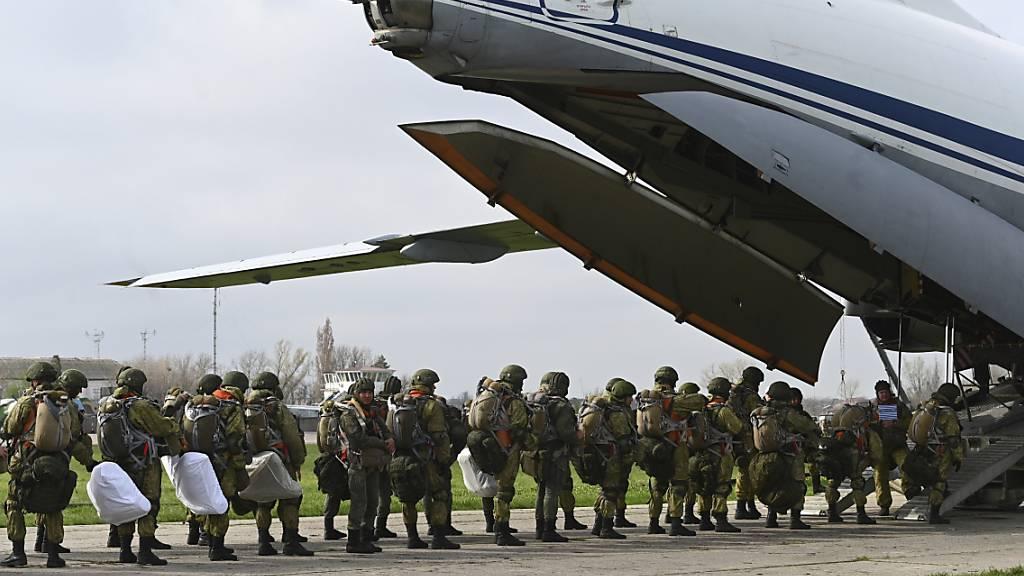 Russische Fallschirmjäger steigen in ein Flugzeug für Luftlandeübungen während Manövern in Taganrog. Foto: Uncredited/AP/dpa