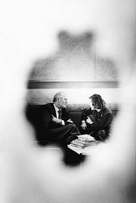 Bundesrat Willi Ritschard und die spätere Bundesrätin Elisabeth Kopp fotografiert durch ein Türfenster (1981).