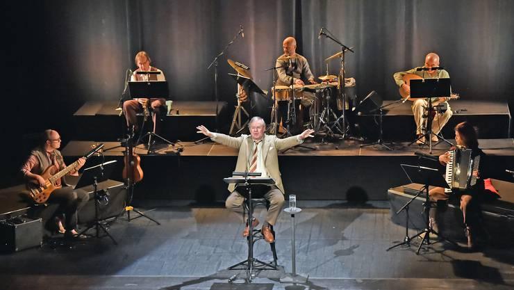 Joachim Król auf einem Barhocker; hinter und neben sich das fünfköpfige L'Orchestre du Soleil.