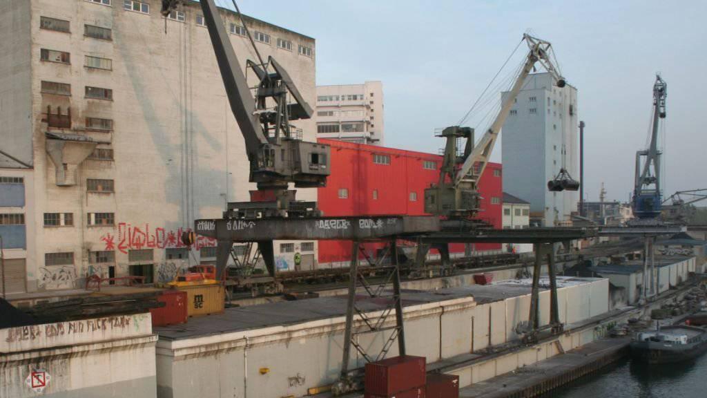 Der Kran links vor dem Betonsilo im inzwischen aufgehobenen Basler Rheinhafen St. Johann bekommt am gegenüberliegenden Ufer eine neue Bleibe. Derzeit an Land eingelagert, wird er im August wieder aufgebaut.