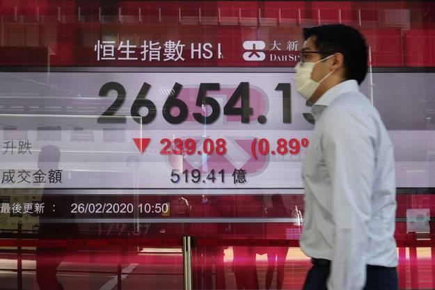 Ein Händler mit Schutzmaske an der Börse in Hong Kong, wo die Kursrückgänge besonders deutlich waren.