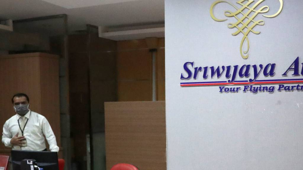 Ein Mitarbeiter steht am Soekarno-Hatta International Airport in der Nähe des Sriwijaya Air-Logos. Foto: Tatan Syuflana/AP/dpa