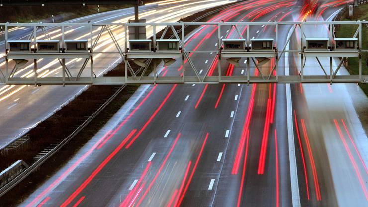 Autos fahren unter einer Mautbrücke über der Autobahn A5 bei Frankfurt. (Archiv)