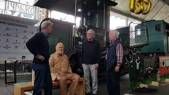 Besucher diskutieren über Niklaus Riggenbach (in Holz, sitzend) vor der Lok 7