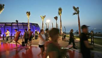 Touristen auf einer Strandpromenade im Emirat Dubai, einem der sieben Emirate der Vereinigten Arabischen Emirate (VAE) am Persischen Golf. Künftig soll eine Glücksministerin die Menschen im Land glücklicher machen (Archiv)