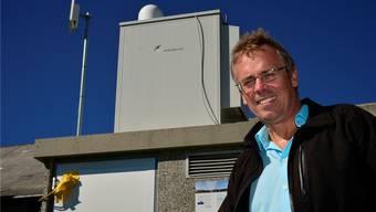 Per Just, Geschäftsführer der SWG, vor der Anlage auf dem Obergrenchenberg. Links sieht man die Richtstrahlantenne, in der Mitte die Radaranlage.