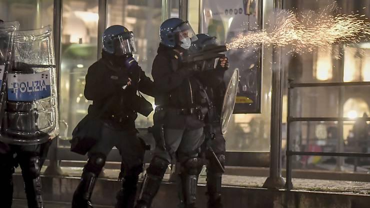 Polizisten setzen während eines Protests gegen die Corona-Maßnahmen der Regierung in Turin Tränengas ein. Foto: Claudio Furlan/LaPresse/AP/dpa