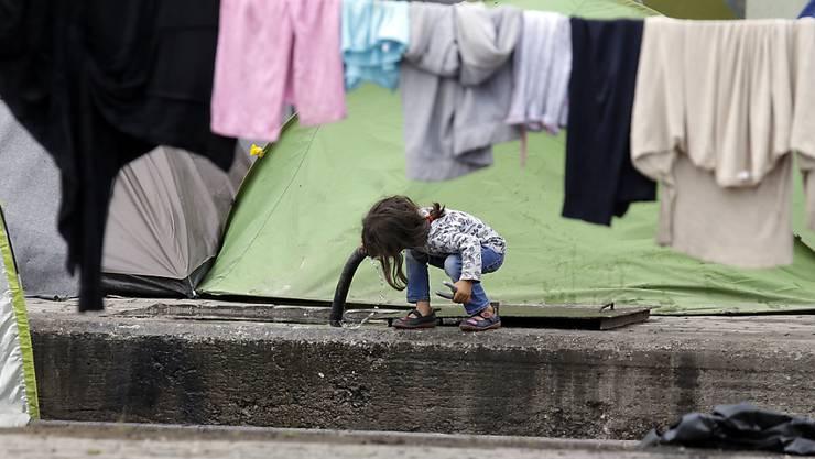 Ein Mädchen trinkt in einem griechischen Flüchtlingslager bei Idomeni Wasser aus einem Schlauch: Die EU-Kommission hat am Mittwoch einen Fairness-Mechanismus zur Verteilung von Flüchtlingen vorgeschlagen, um Länder wie Griechenland zu entlasten (Archiv).