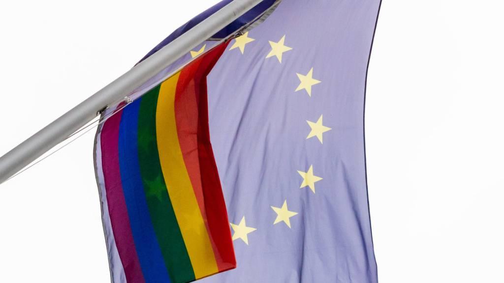 Eine Regenbogenfahne weht neben der EU-Flagge an der der Vertretung der Europäischen Kommission in Berlin. Foto: Christoph Soeder/dpa