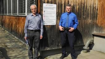 Walter Jucker und Hansueli Loosli (r.) vor einem Schild, das unter anderem auf das Hanfverbot auf Schulanlagen hinweist. mf