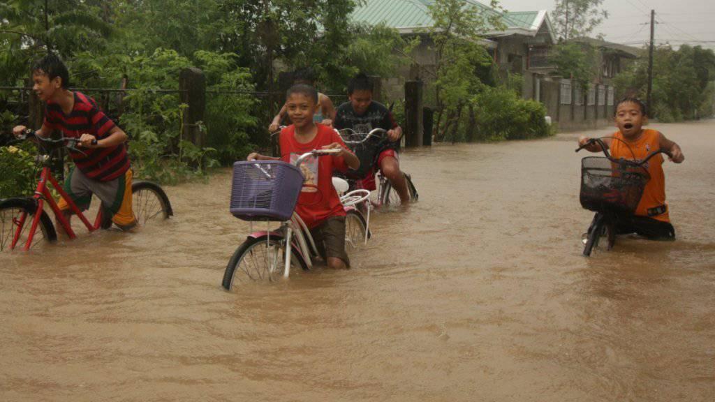 Schwieriges Vorankommen auf überschwemmten Strassen in Baccara auf den Philippinen.