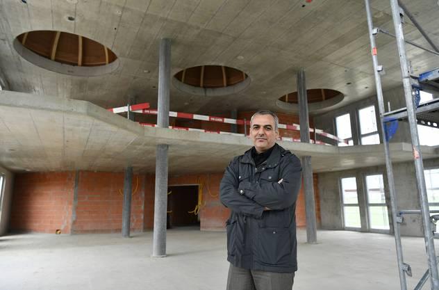 Projektleiter Nadir Polat im Hauptraum der Moschee mit der Galerie im Hintergrund, die den Frauen vorbehalten ist.