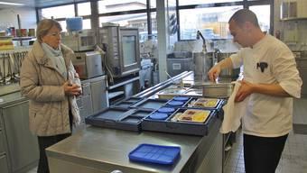 Rosmarie Jufer holt die ersten drei Menüs des neuen Mahlzeitendienstes bei Christian Diriwächter in der Küche des Alterszentrums Burkertsmatt ab.