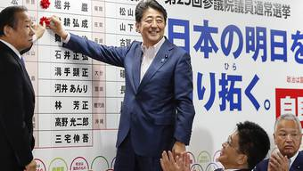Regierungschef Shinzo Abe markiert die Namen der gewählten Kandidaten seiner Liberaldemokratische Partei LDP mit roten Rosen.