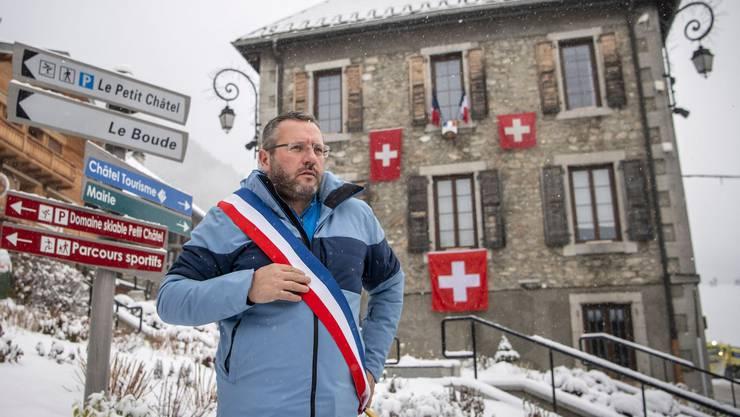 Frankreichs Farben umgehängt, das Schweizer Kreuz am Rathaus: Châtels Gemeindepräsident Nicolas Rubin.