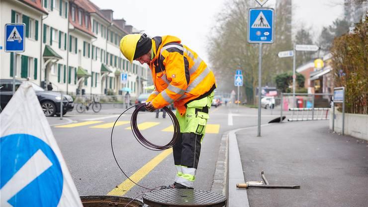 Ein Arbeiter verlegt Leitungen für das Basler Glasfasernetz.