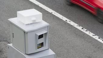 Eine Radarfalle blitzt ein Fahrzeug (Symbolbild)