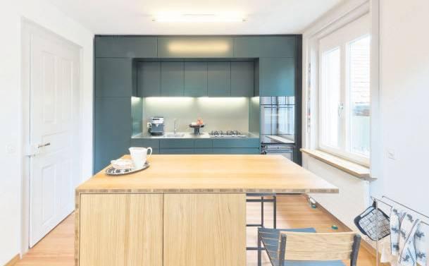 Die offen gestaltete Küche strahlt in ruhigem «Tief-grün». Das Eichenholz der Kochinsel ergänzt das Bild.