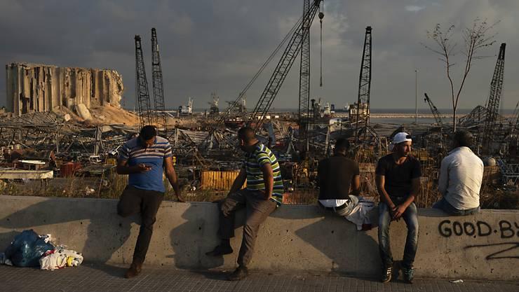 dpatopbilder - Menschen sitzen in der Nähe des Ortes der verheerenden Explosion im Hafen Beiruts. Foto: Felipe Dana/AP/dpa