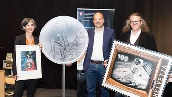 50 Jahre Mondlandung: Nicola von Greyerz von der Uni Bern zeigt das Jubiläumssignet der Hochschule, Christoph Tanner von Swissmint die Sondermünze und Bernhard Kallen von der Post die Sondermarke.