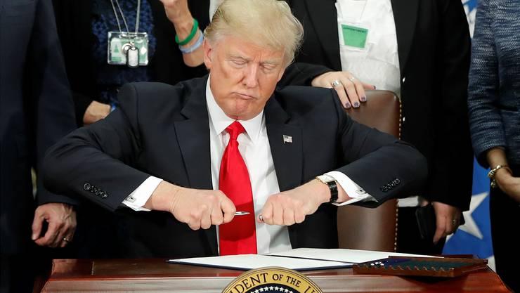Wenn er seinen Stift zückt, zittert die Welt:US-Präsident Donald Trump verunsichert mit seiner Wirtschaftspolitik auch Schweizer Unternehmen. Keystone
