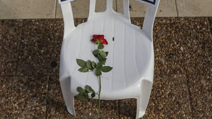 Ein Plastikstuhl mit einer roten Rose und einem Zettel mit dem Namen eines Menschen, der an Covid-19 verstorben ist, steht auf dem Rabin-Platz. Die Zahl der Todesfälle in Israel im Zusammenhang mit einer Corona-Infektion hat die Marke von 1000 überschritten. Foto: Ilia Yefimovich/dpa