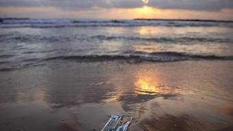 Ein Mundschutz liegt am Strand von Tel Aviv. Foto: Oded Balilty/AP/dpa