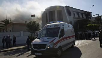 Ein Krankenwagen fährt Verletzte weg. Aus dem Gebäude des Aussenministeriums in Tripolis stieg nach dem Anschlag Rauch auf.