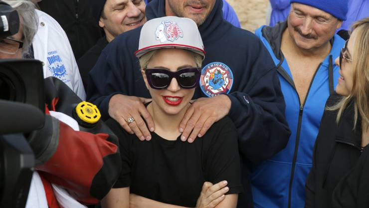 """Lady Gaga, Mitte, und ihr Verlobter, der """"Chicago Fire""""-Star Taylor Kinney (dahinter) am Sonntag beim Polar Plunge."""