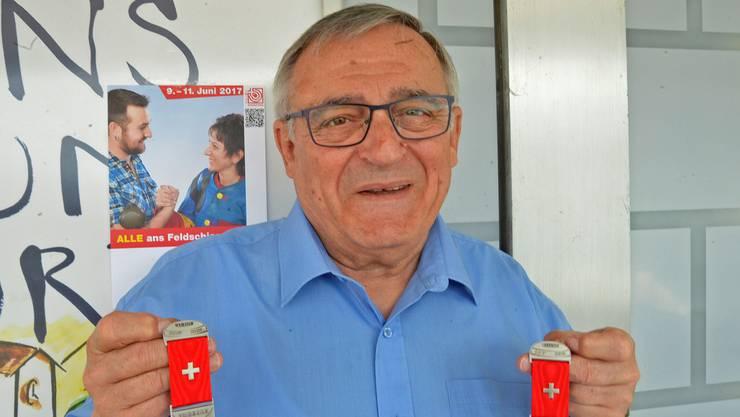 Werner Stauffer präsentiert die Kranzabzeichen für das Feldschiessen.