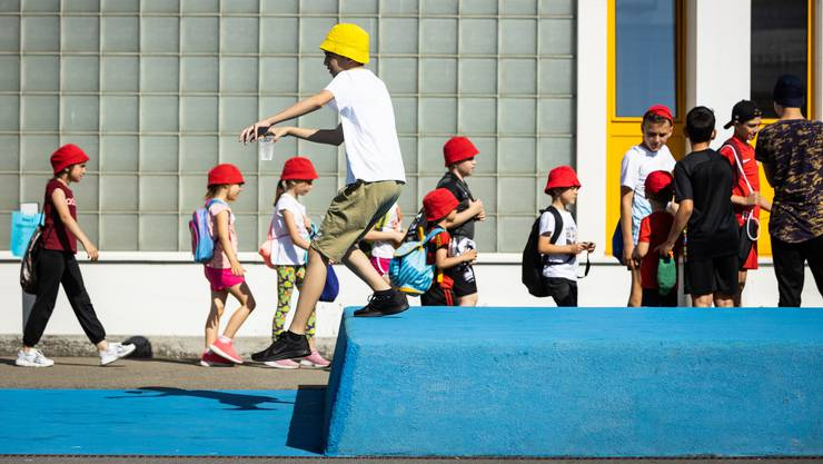 Die farbigen Hüte der Schülerinnen und Schüler hatten eine doppelte Verwendung: Einerseits schützten sie vor der starken Sonne, und anderseits zeigten sie an, zu welcher Gruppe die Kinder gehörten.