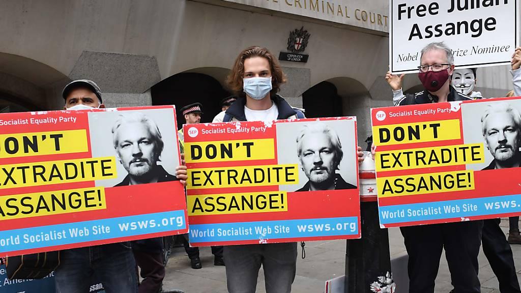 Demonstranten stehen mit Plakaten mit der Aufschrift «Don't Extradite Assange» (dt. Liefert Assange nicht aus) vor dem Old Bailey Gericht, im Vorfeld einer Anhörung im Kampf des Wikileaks-Gründers gegen die Auslieferung an die USA. Foto: Stefan Rousseau/PA Wire/dpa