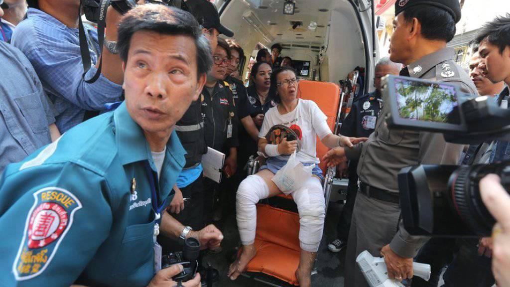 Eine verletzte Frau (m) wird von Rettungskräften umsorgt. Bei der Explosion eines Taxiboots in Bangkok wurden mehrere Menschen verletzt