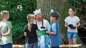 Die Wohler Kinder bringen Obelix Dinge, die er haben möchte. Ein Römer möchte an die Zaubertrank-Zutaten.