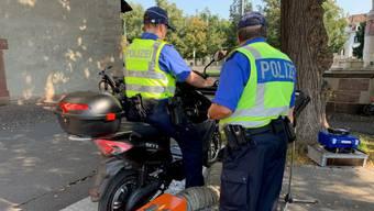 Polizisten kontrollieren bei einen Elektroroller die mögliche Höchstgeschwindigkeit.
