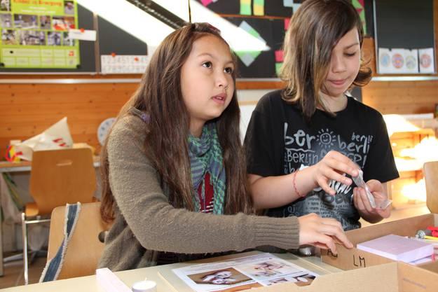 Alexandra und lea informieren sich an der Beamer-Projektion, wie sie das Tuc Tuc bauen müssen