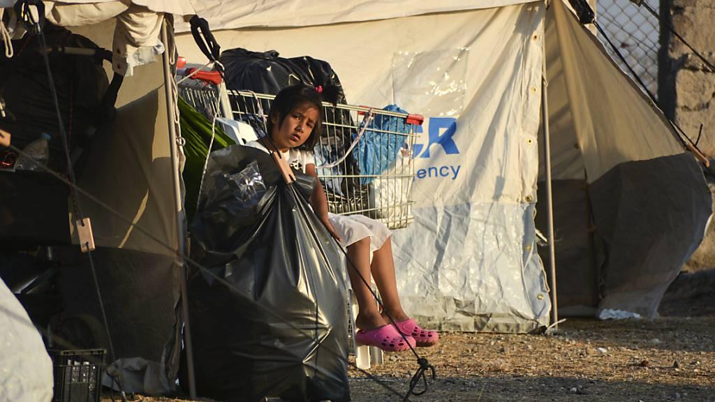 Ein Kind sitzt im neu errichteten temporären Flüchtlingslager in Kara Tepe neben einem Zelt. Auf der griechischen Insel Lesbos sind knapp drei Viertel der 12 000 Migranten aus dem abgebrannten Camp Moria in ein provisorisches Zeltlager gezogen. Foto: Panagiotis Balaskas/AP/dpa