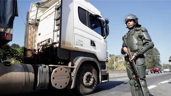 Ein Soldat schützt Trucker in São Paulo: Vereinzelt nehmen die brasilianischen Lastwagenfahrer mit Militäreskorte die Arbeit wieder auf.