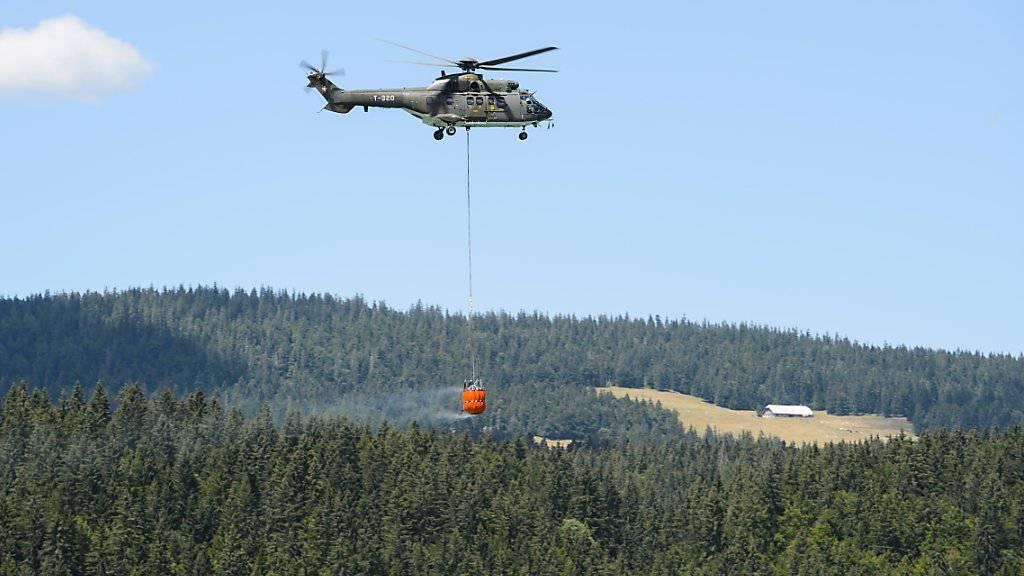 Ein Helikopter auf dem Weg zu einem der acht Wasserbecken im Waadtländer Jura. (Archiv)