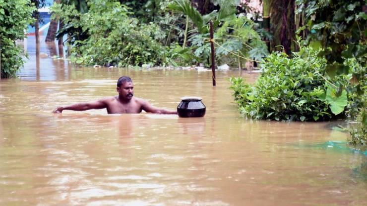 Ein Mann watet durch eine überflutete Strasse in der Stadt Kochi im Bundesstaat Kerala.