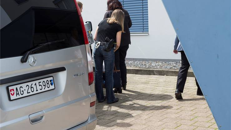 Beamte in Zivil laden beschlagnahmte Gegenstände in ein Fahrzeug mit Aargauer Kennziffer.