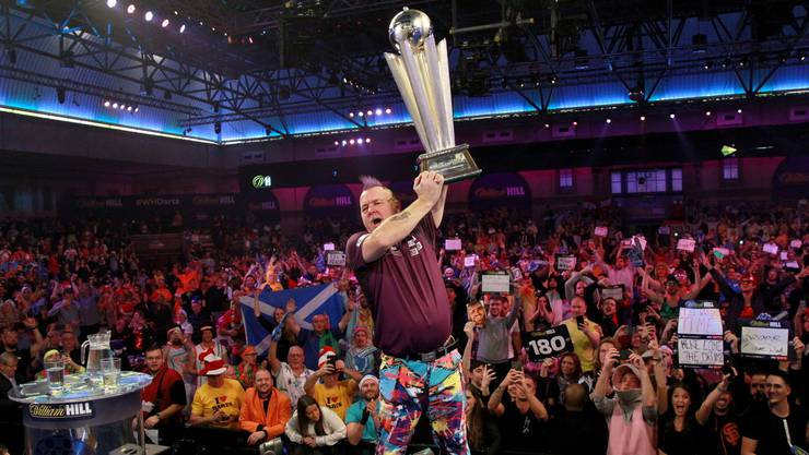 Grosser Moment: Peter Wright stemmt den WM-Pokal in die Höhe - das Publikum feiert.