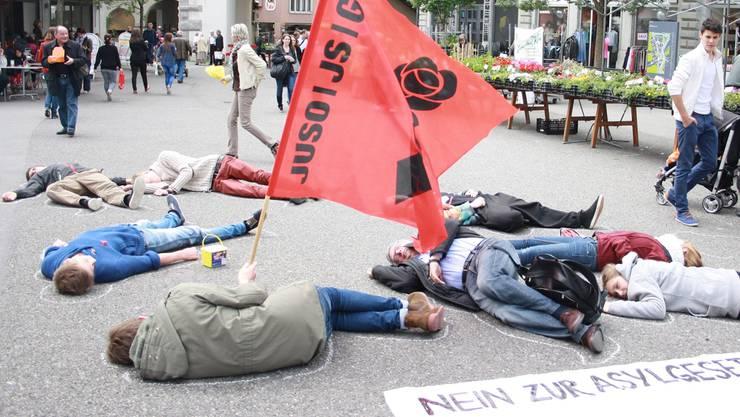 Rund 10 Personen der JUSO Aargau legten sich auf den Boden und liessen den Umriss ihrer Körper mit Kreide nachzeichnen.