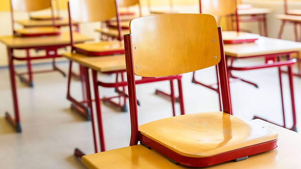 Stühle stehen auf den Tischen in einem leeren Klassenzimmer. Foto: Philipp von Ditfurth/dpa