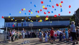 Statt eines Spatenstichs zum Start der Bauarbeiten an der neuen Turnhalle lassen die Islisberger Kinder Ballons in den Gemeindefarben steigen.