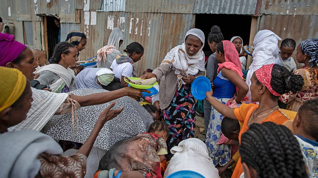 Vertriebene aus der Region Tigray stehen Schlange, um von Anwohnern gespendete Lebensmittel in einem Aufnahmezentrum für Binnenvertriebene zu erhalten. Foto: Ben Curtis/AP/dpa