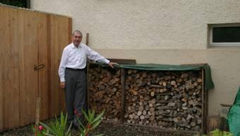 Willi Berchtold steht neben seinem kontrollierten Feuerholzstapel hinter seinem Einfamilienhaus in Brugg.   ahu